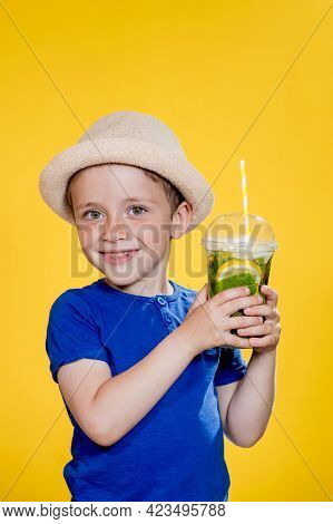 Cute Boy Drink Mojito Cocktail From Plastic Cup Over Yellow Studio Background