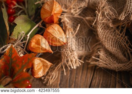 Close-up Wreath Autumn Leaves And Natural Materials On Rustic Boards. Top View Round Wreath Autumn H