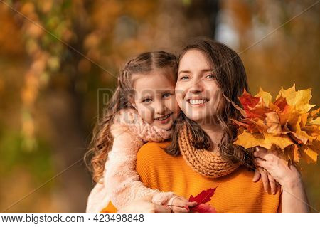 Happy Family! Mother And Daughter Hugging And Playing And Laughing At The Autumn Stroll. The Girl Hu
