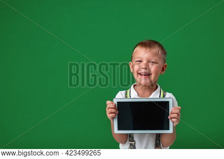 Small Boy Shows Off New Computer Tablet, Holding It Out In Front Green Background. Smiling Preschool