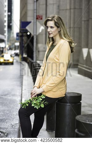 Holding A Bunch Of Green Leaves And Sitting One Of Stakes On The Street, A Young Pretty  Woman Is Wa