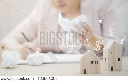 Businesswoman Hand Write Note On Paper With Mini Wood House Model From Model On Wood Table, Planning