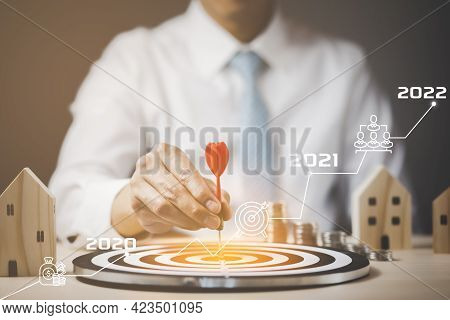 Targeting The Business And 2022 Concept, Businessman Touch Red Arrow Dart To The Virtual Target Dart