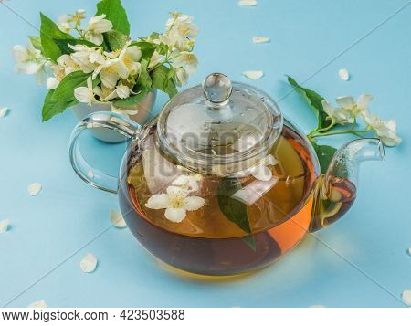 A Glass Teapot And Jasmine Flowers On A Blue Background. An Invigorating Drink That Is Good For Your
