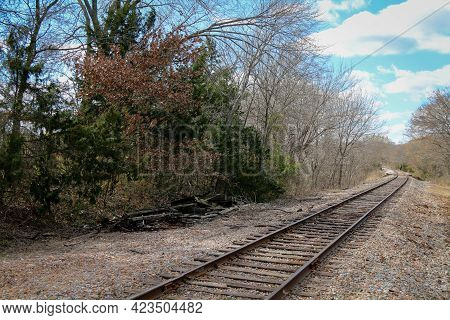 A Rural Country Railroad Train Tracks Leading Through Countryside With Blue Sky And Green Trees.