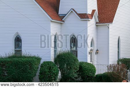 A Rural Village Church Building Facade Painted Bright White With Lush Bush Shrubs Arched Stain Glass