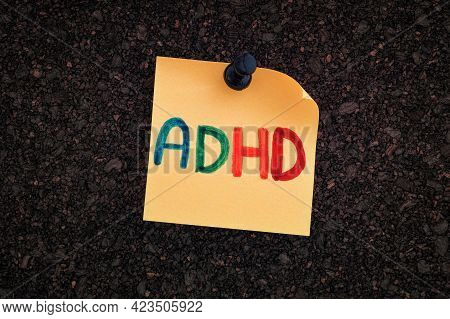 Adhd. The Abbreviation Adhd Written On A Yellow Paper Note Pinned To A Cork Board. Close Up. Adhd Is