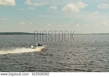 A Small, White Motorboat Floats At High Speed On The Water.