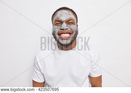 Indoor Shot Of Joyful Afro American Man Grins At Camera Shows White Teeth Applies Clay Mask For Skin