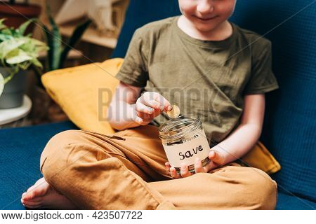 Close Up Of Little Child Kid Boy Hands Grabbing And Putting Stack Coins In To Glass Jar With Save La