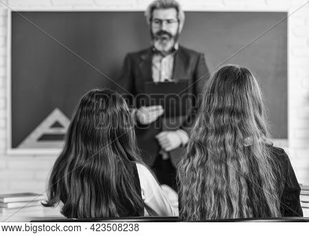 Elementary Pupil With Teacher In Classroom. Discussion Group Of Children And Teacher. Teacher And Ch