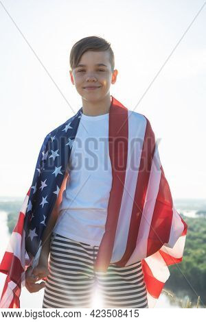 Blonde boy waving national USA flag outdoors over blue sky at the river bank. Beauty summer sunny day. American flag, patriotism, independence day 4th july concept