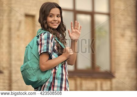 Cute Happy Girl With Long Hair In Casual Style Carry Travel Bag Waving Goodbye Hand Gesture Outdoors