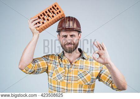 Labor Or Workers Day. Man Laborer With Brick. Guy Wear Worker Uniform. Handsome Builder In Helmet