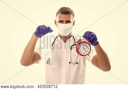 Time To Stay Home. Man Hold Clock. Alarm. Doctor In Respirator Mask Isolated On White. Coronavirus P