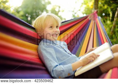 Cute Little Blond Caucasian Boy Reading Book And Having Fun With Multicolored Hammock In Backyard Or