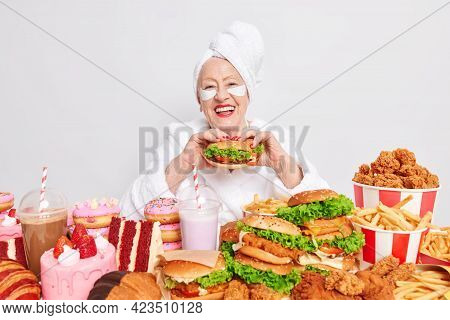 Time For Snack. Happy Old Lady Eats Appetizing Hamburger Smiles With Cheerful Expression Applies Bea