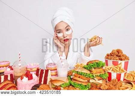 Serious Young Asian Woman Looks Directly At Camera Holds French Fries Poses Near Table Full Of Harmf