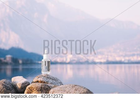 Hyaluronic Acid, Serum Skincare Glass Bottle On Stone, Mountain Lake Background. Serum Product Cosme
