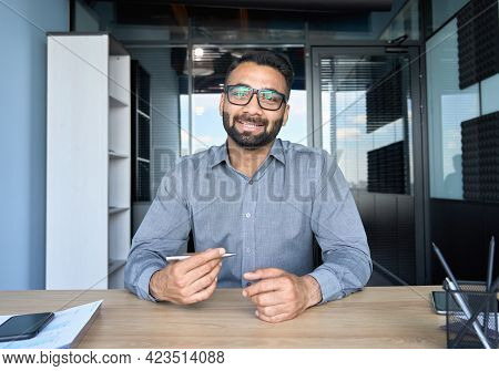 Smiling Indian Businessman In Glasses Talking To Camera At Work By Video Call Conference. Financial