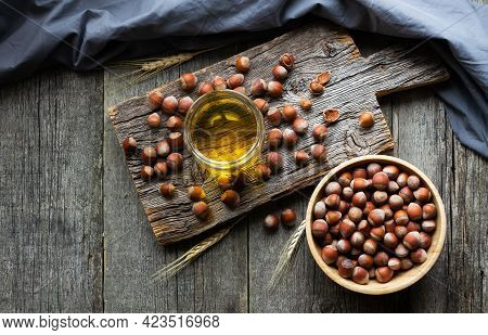 Hazelnut Oil, Filbert And Cooking Oil In Glass Of Jar On Wooden Backdrop, Heap Or Stack Of Hazelnuts