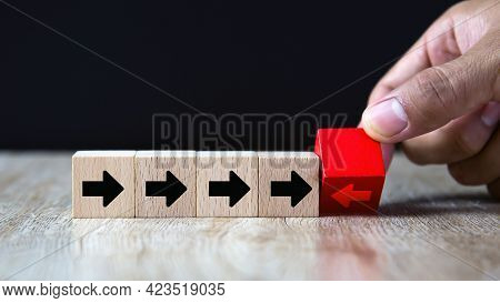 Close-up Hand Chooses Arrow Icon On Cube Wooden Toy Block Stacked With Pointing To Opposite Directio