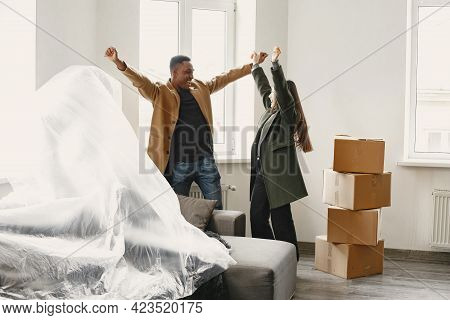 Happy Couple Unwrapping Furniture In New Flat