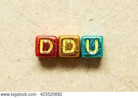 Metallic Color Alphabet Letter Block In Word Ddu (abbreviation Of Delivered Duty Unpaid) On Wood Bac