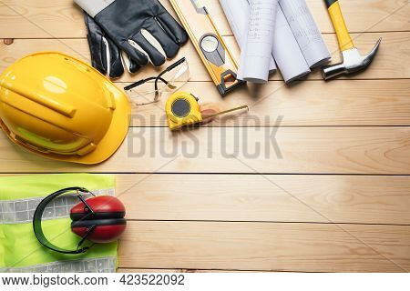 Work Safety. Standard Construction Site Protective Equipment On  Top View Wooden Background, Flat La