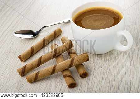Teaspoon, Coffee With Milk In White Cup, Few Brown Striped Wafer Rolls With Chocolate Filling On Woo