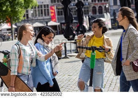 Lifestyle Portrait Of A Diverse Multiethnic Group Of Four Young Girl Friends On The Electro Scooter