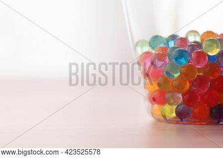 Translucent colors. Colorful polymer beads or spheres in a thin glass cup with incoming light.
