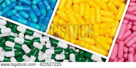 Top View Of Colorful Capsule Pills In Plastic Box. Pink, Yellow, Blue, Green-white Capsule Pills In