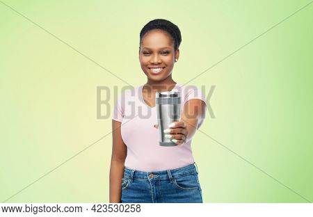 sustainability, eco living and people concept - portrait of african american woman in turquoise shirt with thermo cup or tumbler for hot drinks over green background