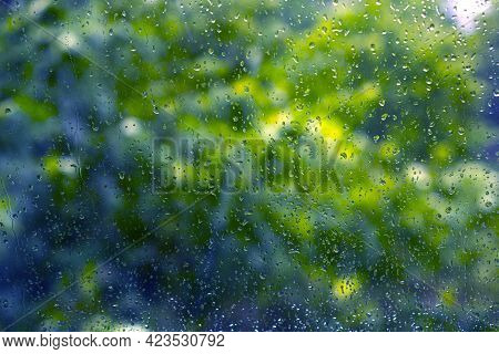 Raindrops. Wet Window Glass During The Rain. Green Leaves Of Trees Out Of Focus. Focus Is On The Rai