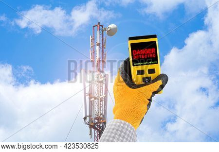 Measuring Electromagnetic Radiation From A Cell Tower. The Device Indicates Hazardous Radiation With