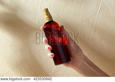 beauty, cosmetics and bodycare concept - close up of hand with bottle of sunscreen oil over beige background with shadows