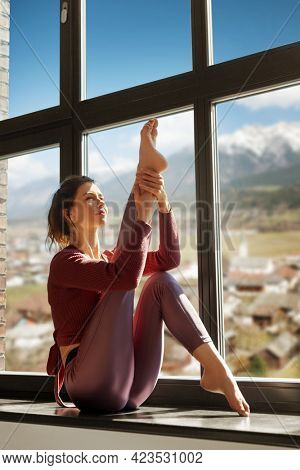 fitness, sport and healthy lifestyle concept - woman doing yoga exercise on window sill at studio over suburban view and alps mountains on background