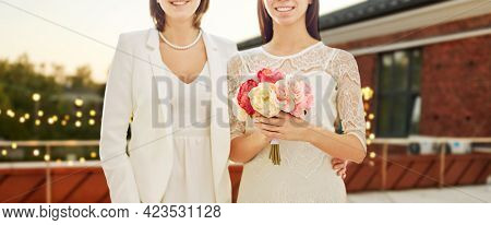 homosexuality, same-sex marriage and wedding concept - close up of happy married lesbian couple with flower bunch over roof top party background