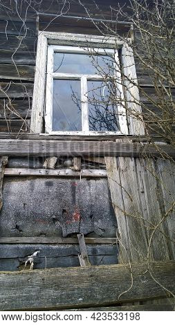 Old Abandoned Wooden House With Broken Window In Disrepair From Fairy Tale. Dirty Building Exterior