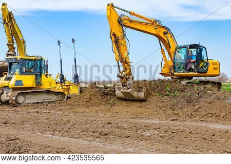 Two Excavators And Bulldozer Are Moving Earth To Level, Equates Building Site.