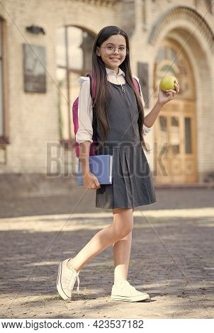 Focus On Dieting. Happy Child Hold Apple And Book Outdoors. School Snack. Health Education. Healthy