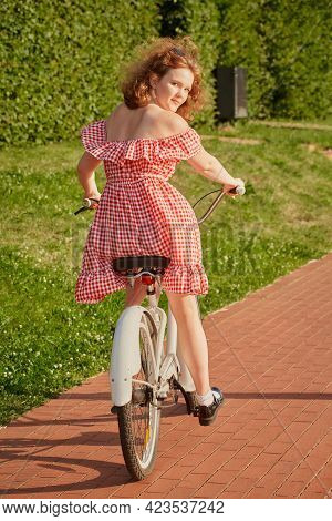 Beautiful Pinup Girl With Red Dress And Curly Red Hair Moves On Bike At Sunny Park In Sun Light