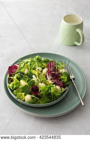 Top View Of A Table And A Plate With Light Salad, Green Mix Salad With Broccoli, Mozzarella Cheese A