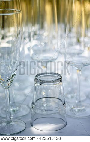 Close Up Of Different Glasses, Champagne Glasses And Cocktail Glass On A Table With White Tablecloth