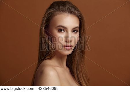 Seductive Young Woman With Bare Shoulders At Brown Wall