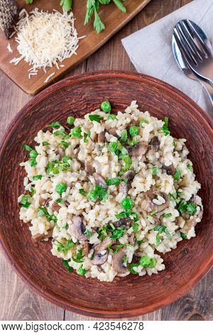 Risotto With Arborio Rice, Brown Button Mushrooms And Green Peas, Garnished With Fresh Parsley, Vert