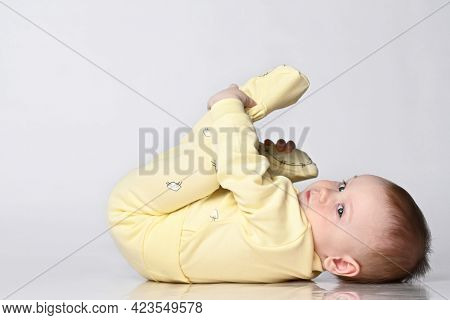 Baby Lying On His Back, Happy Infant Wearing A Yellow Bodysuit Jumpsuit, Beautiful Baby Lying On A W