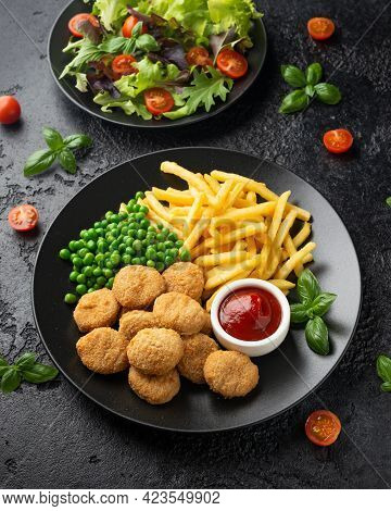 Fried Crispy Chicken Nuggets With Ketchup, French Fries And Green Peas In Black Plate