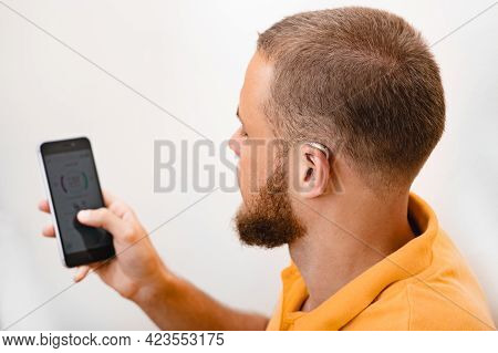 Hearing Impaired Man Adjusts Settings For His Bte Hearing Aid Via Smartphone. Hearing Aids, Deafness